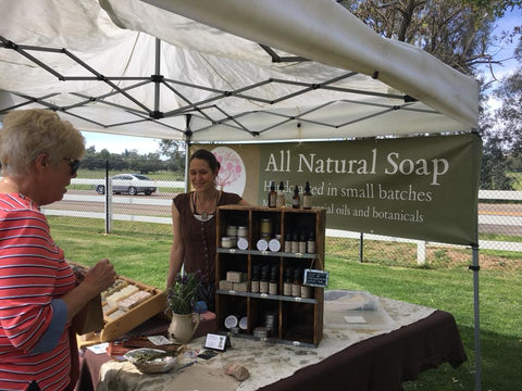 woman at farmer's market booth with customer selling soap