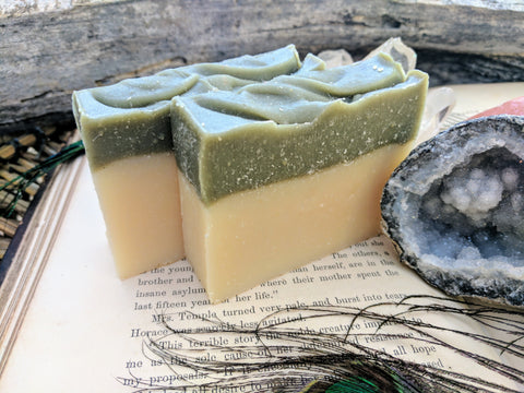 green and white soap on an antique book with geode and peacock feather