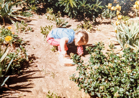 Apryl Martinez founder of Plum Brilliance as a child smelling flowers