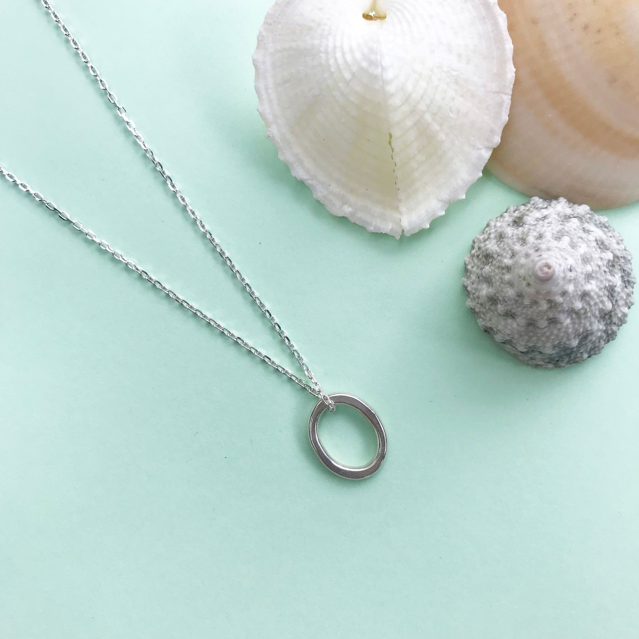 sterling silver pebble pendant with polished finish and choice of chain lengths, made by Ami of AB Jewellery, Goldsmith
