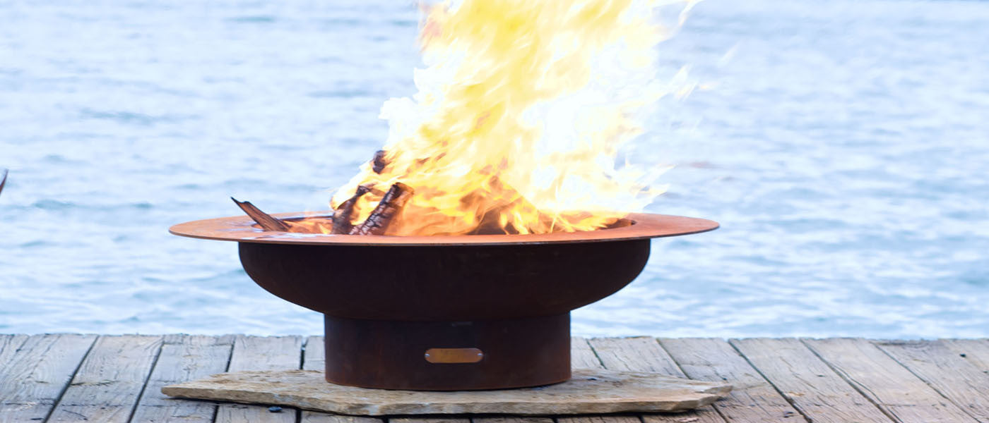 fire pit with burning wood at lake
