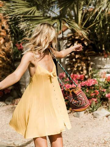 Yellow strap mini dress billowing in the breeze