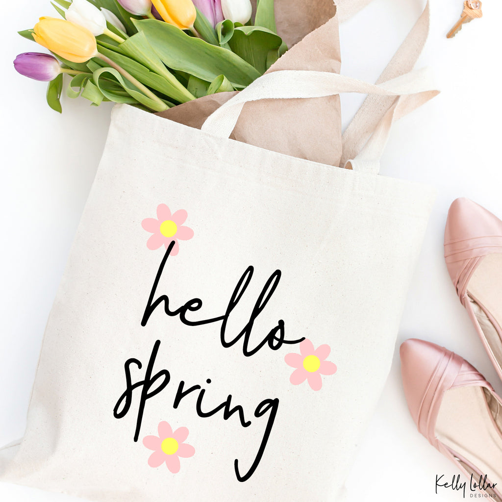Canvas tote with the flowers from the Sleepy Bunny svg file in pink and yellow plus added Hello Spring quote in black