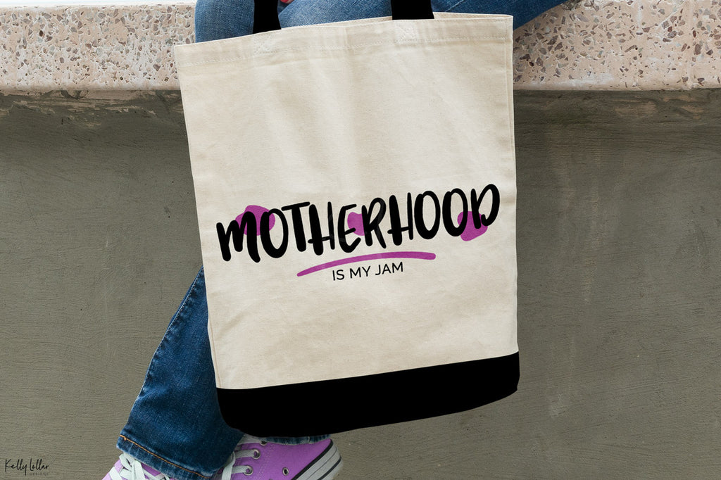 Canvas tote with the Motherhood Is My Jam svg in black and purple