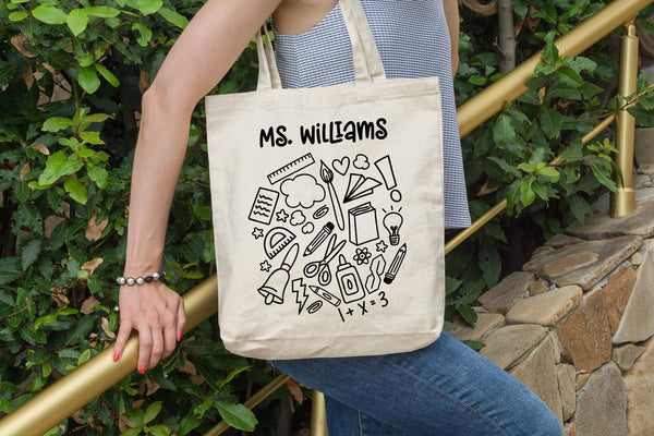 Canvas tote with the School Doodle Cloud svg cut file in black and added teacher's name