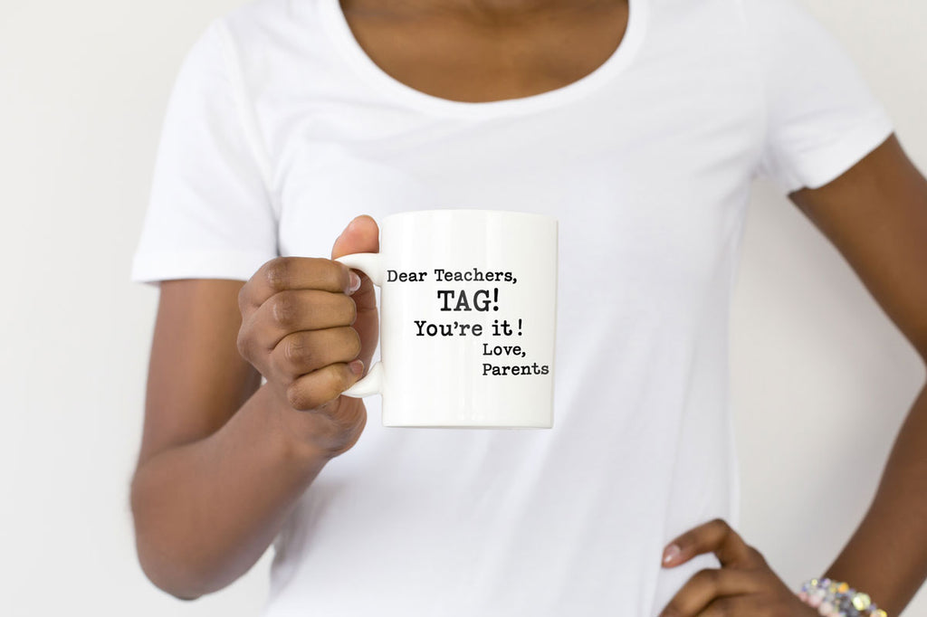 Woman holding a mug with the Dear Teachers, Tag! You're It! Love Parents svg cut file
