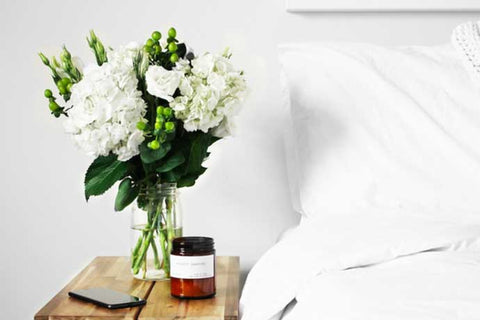 Flowers displayed on bedside cabinet next to bed with white sheets