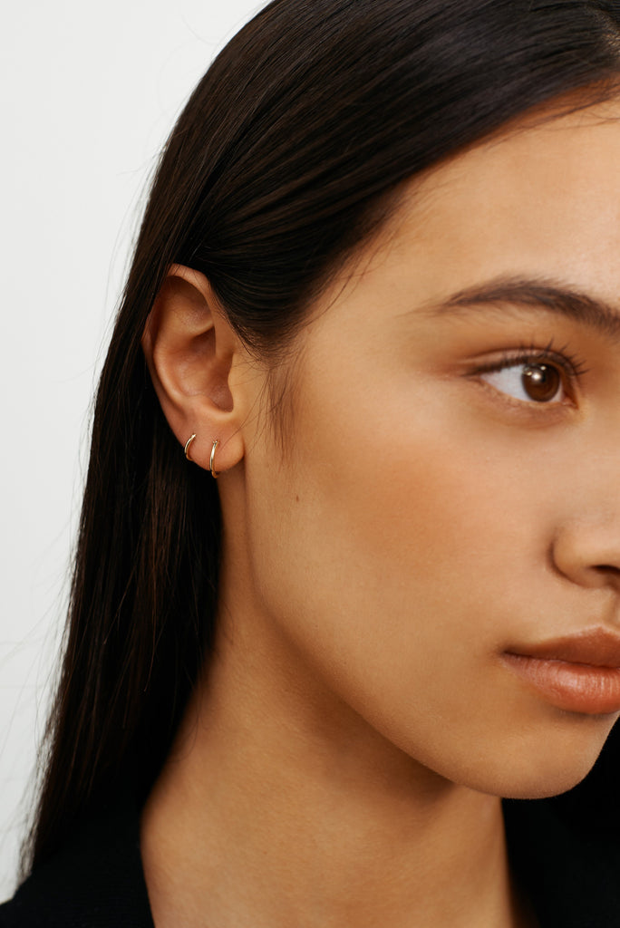 Cropped view of model wearing 14K 1M Hoops Earrings Bagatiba
