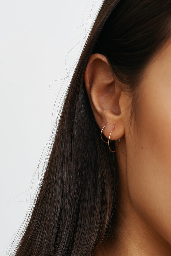 Cropped view of models ear 14K 301 Mini Hoops Earrings paired with size 302 Bagatiba