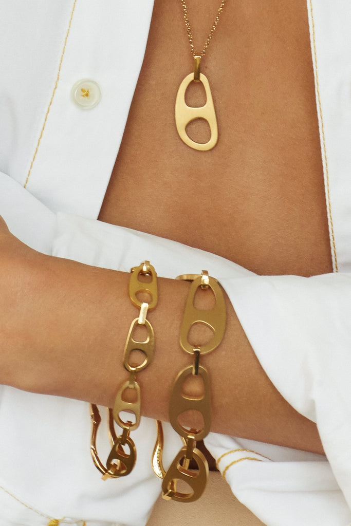 Zoomed view on model of Adjustable Gold Tab Necklace and two tab bracelet styles  bagatiba