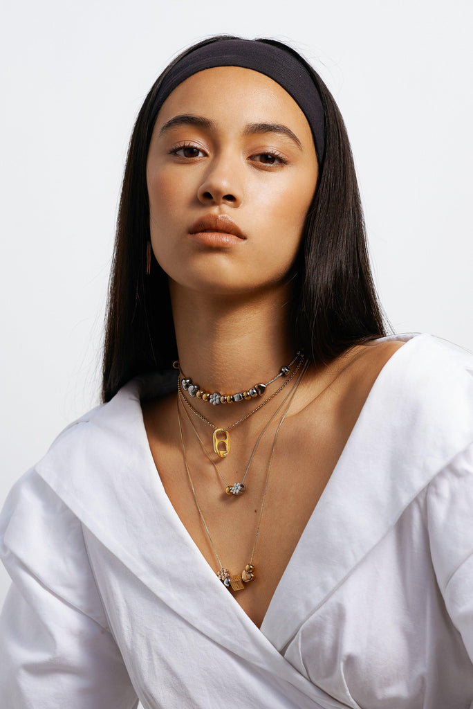 "Model wearing 4 necklaces layered with ""A"" Letter Block letter Bagatiba"