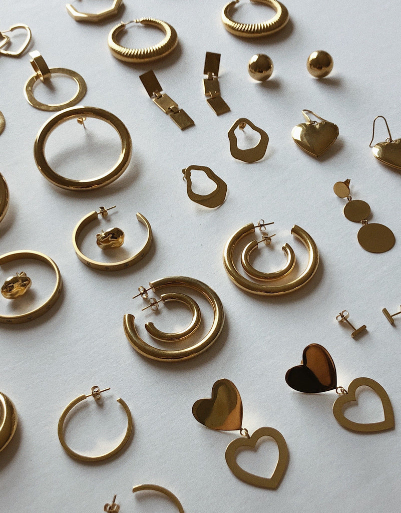 Flat lay detail view of eco earrings including Gold Hollow Hoops Earrings Bagatiba
