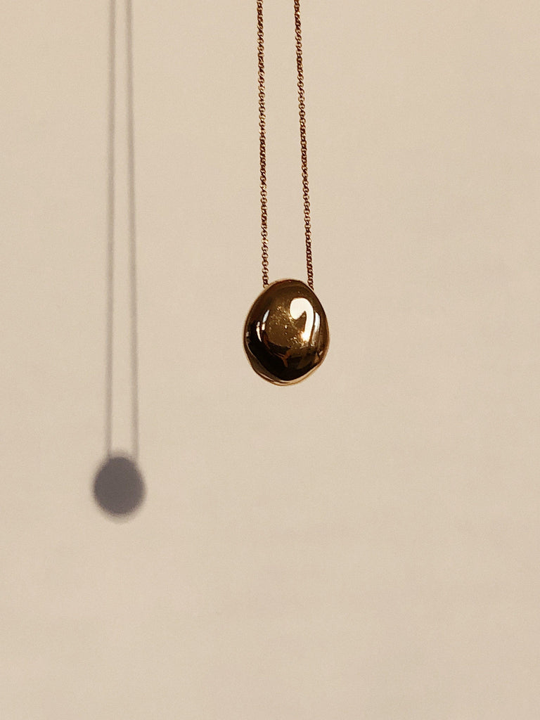Detail view of Gold Orb Necklace in natural light bagatiba