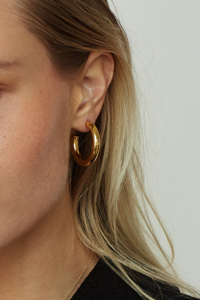 Detail view of model's ear wearing Mini Gold Hollow Hoops Earrings Bagatiba