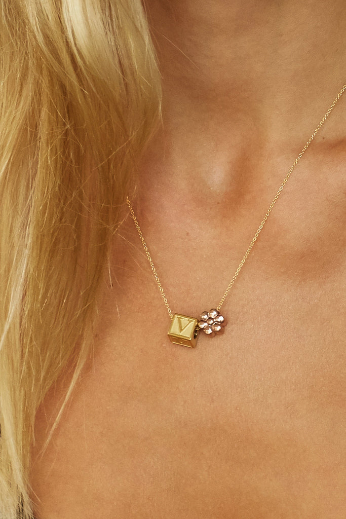 "Cropped view of model wearing ""V"" Letter Block letter and flower bead on chain  Bagatiba"