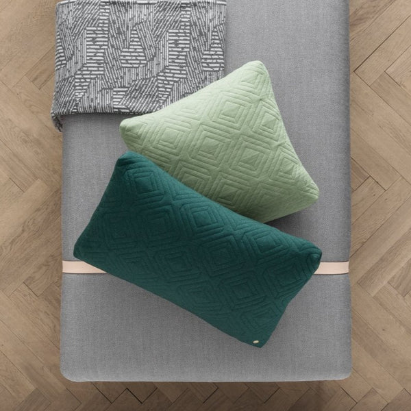 overhead shot of quilt cushion by ferm living in green and dark green