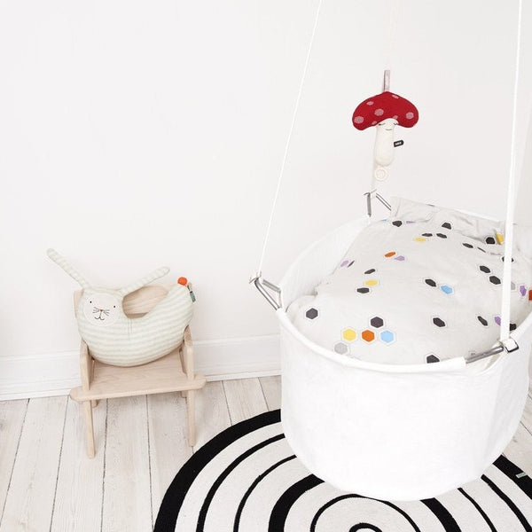 Scandinavian inspired nursery with swinging crib and rabbit peter cushion on a wooden chair.