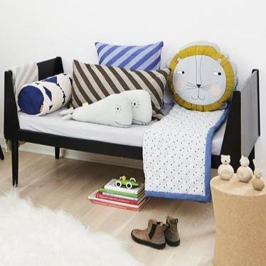 Friendly and Scandinavian inspired children's room styled by Danish design brand OYOY.  A playful collection of animal cushions (whale & lion) and textiles sit on a black bench.
