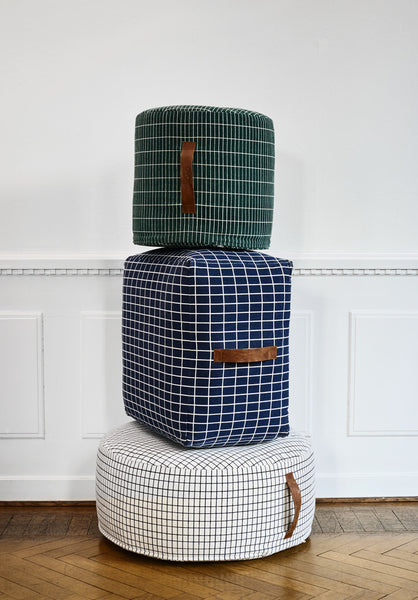 the sit on me pouf styled as a stack with cylinder, square and round shapes piled high in front of a wood panelled wall with parquet flooring.