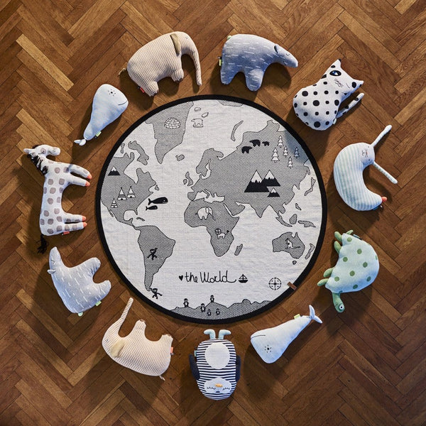 ariel view of the animal cushion collection from the mini range by danish design brand OYOY.  The animals sit in a circular display on parquet flooring surrounding the world map rug.
