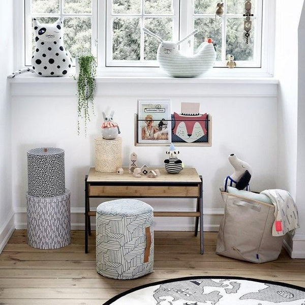 A bright and airy children's room with lots of stylish and design led accessories under a window.  Draped over a storage basket you can see the smilla plaid blanket in off white grey colourway