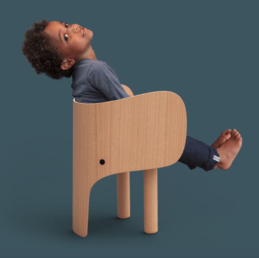 Lifestyle shot of elephant chair designed by Marc Venot.  Simple, stylish and beautiful chair appealing to children and adults alike.  Photo shows young boy sat on the chair.  Ideal teamed with elephant table creating a Scandinavian inspired workspace for kids, inspiring them in creative play.