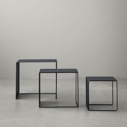 cluster tables black by Ferm Living positioned freestanding in a cluster of 3.  Minimalistic styling with concrete flooring and backdrop.