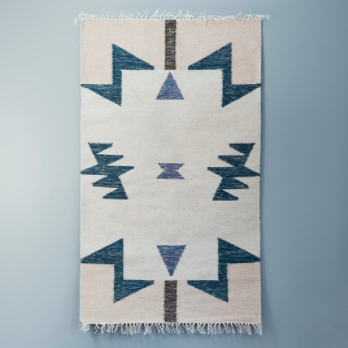 Kelim rug blue triangles from Ferm Living displayed as a wall hanging above a leather armchair.