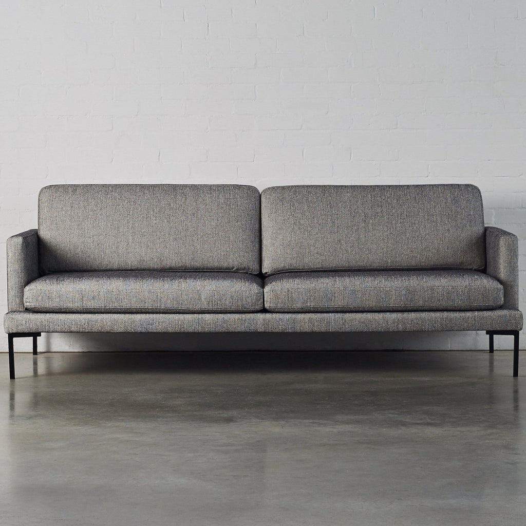 forme 3 seater in atelier 23 monochrome, black legs, concrete floor, white walls
