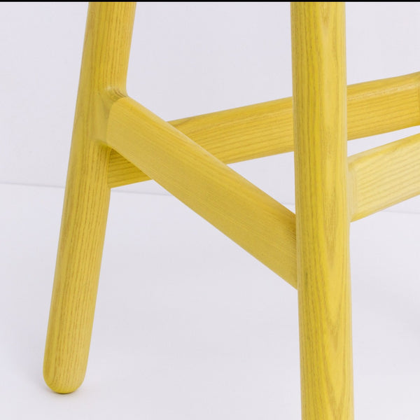 Ninety stool, simple and pure with clever design and detailing, particularly around the footrest.  Providing ergonomic foot support.  Example of practical and beautiful design.  Pictured here a detail shot of the 2 footrest heights in Yellow.