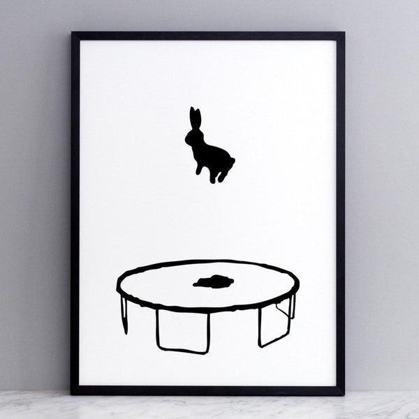 black and white image of HAM rabbit bouncing and playing on his trampoline.  Fun and playful series of prints.  Ideal for adults and children. Pictured here on marble surface with grey painted wall backdrop.