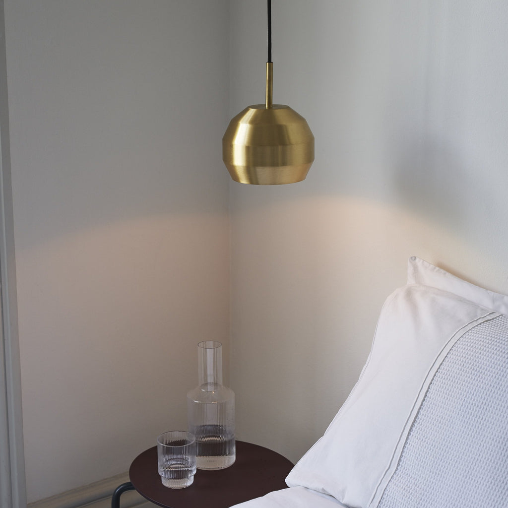 Vitamin Mini Pitch Pendant light in solid brushed brass finish as a bedside light. Available from someday designs