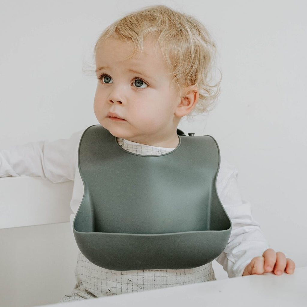 Toddler wearing Boo Chew Bib in graphite, a grey colour