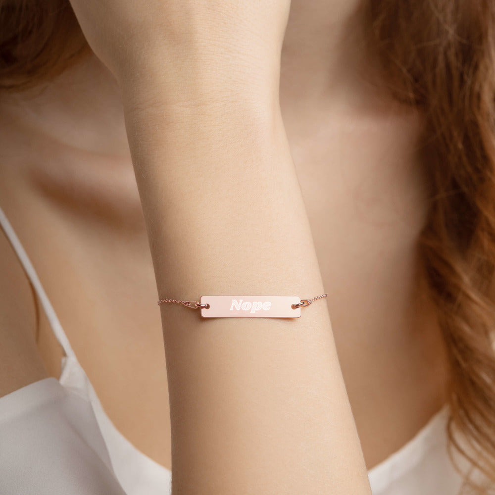 "Rose Gold Silver bar chain bracelet with ""Nope"" engraved. Modeled on an arm."