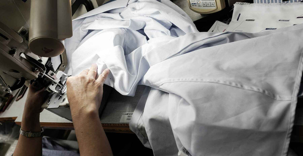 tailor in workshop stitching white custom men's dress shirt