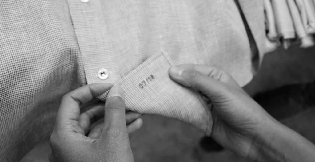 tailor showing stitching of men's custom made-to-measure dress shirt