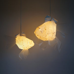 Two geometric lamps in the form of Mommy Goldfish and Baby Goldfish are on.