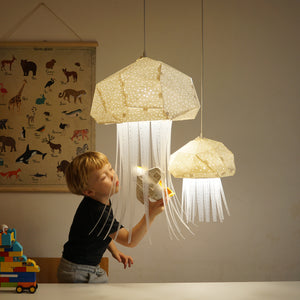 Kid's room where the children, girl and boy, play with geometric lighted lamps which have form of Mommy and Baby Medusa.