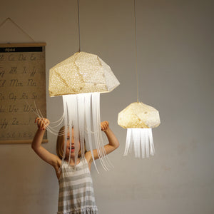 Kid's room where a girl plays with geometric lighted lamps which have form of Mommy and Baby Medusa.