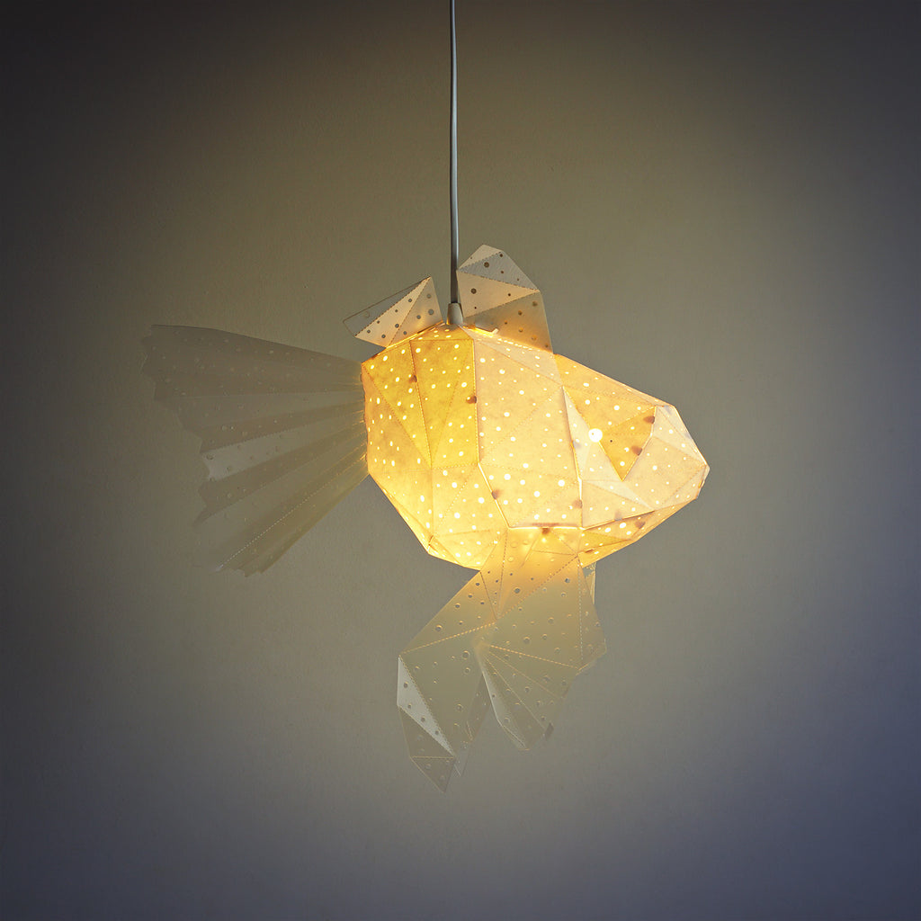 Pendant geometric lamp in the form of a little Goldfish, the light is on.