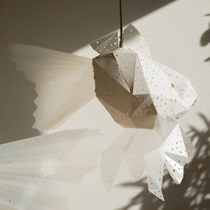 Goldfish lamp hangs in a kids' room, the sunlight casts its shadow on the wall.