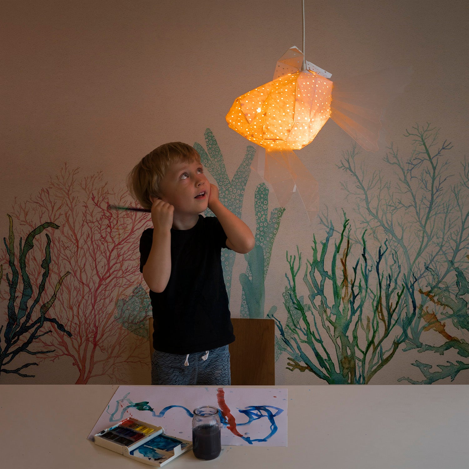 Little boy looks at the pendant lamp, which has a shape of a little Goldfish.