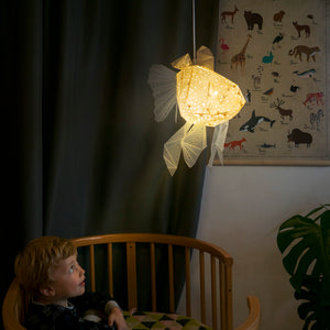 Little boy is watching from his bed a cute pendant lamp in the form of a little Goldfish.
