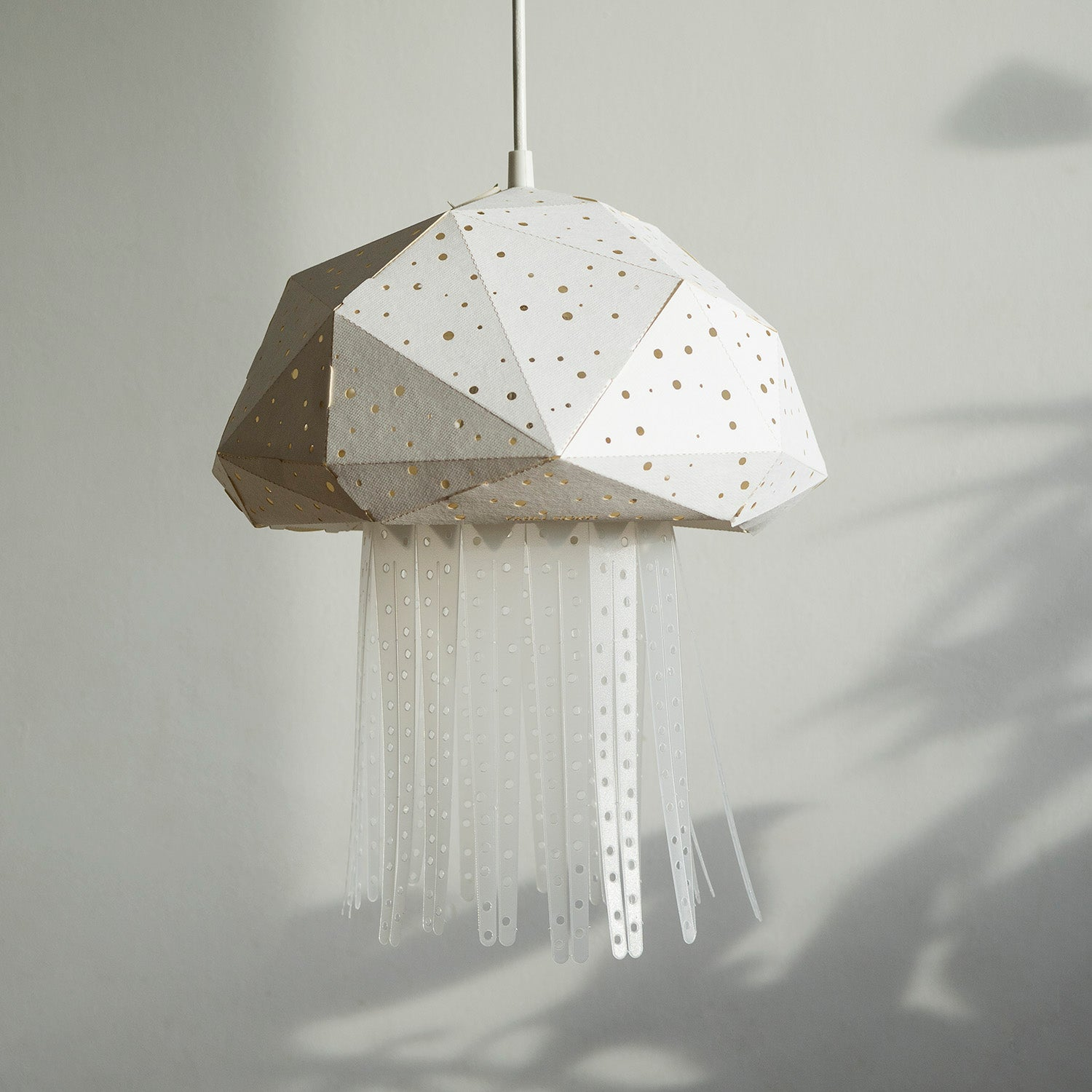 Geometric Jellyfish lamp hangs in the kids' room near the white wall.