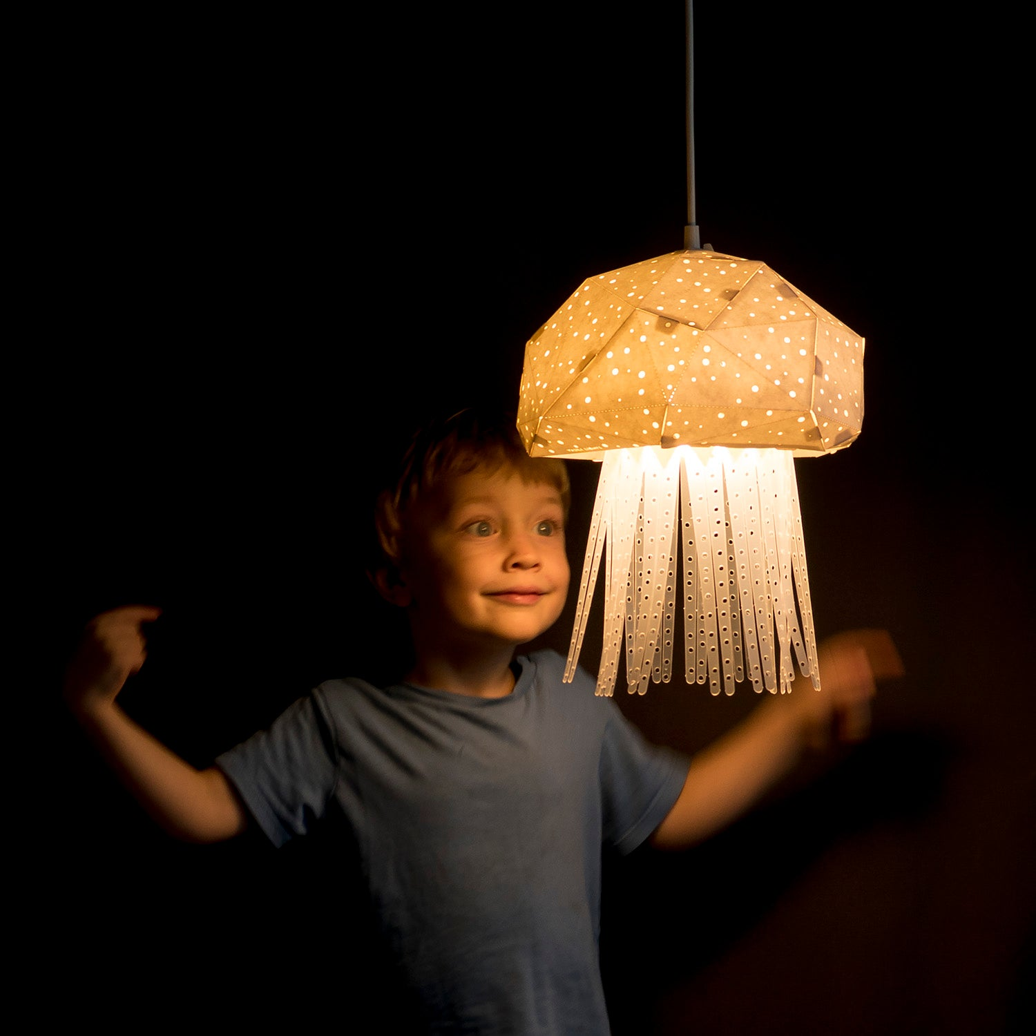 Little boy playing with the pendant sea-inspired lamp, which has a shape of little Jellyfish.