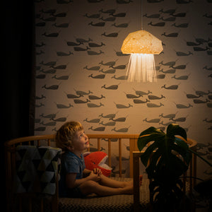 Little boy admires the pendant sea-inspired lamp, which has a shape of a little Jellyfish.