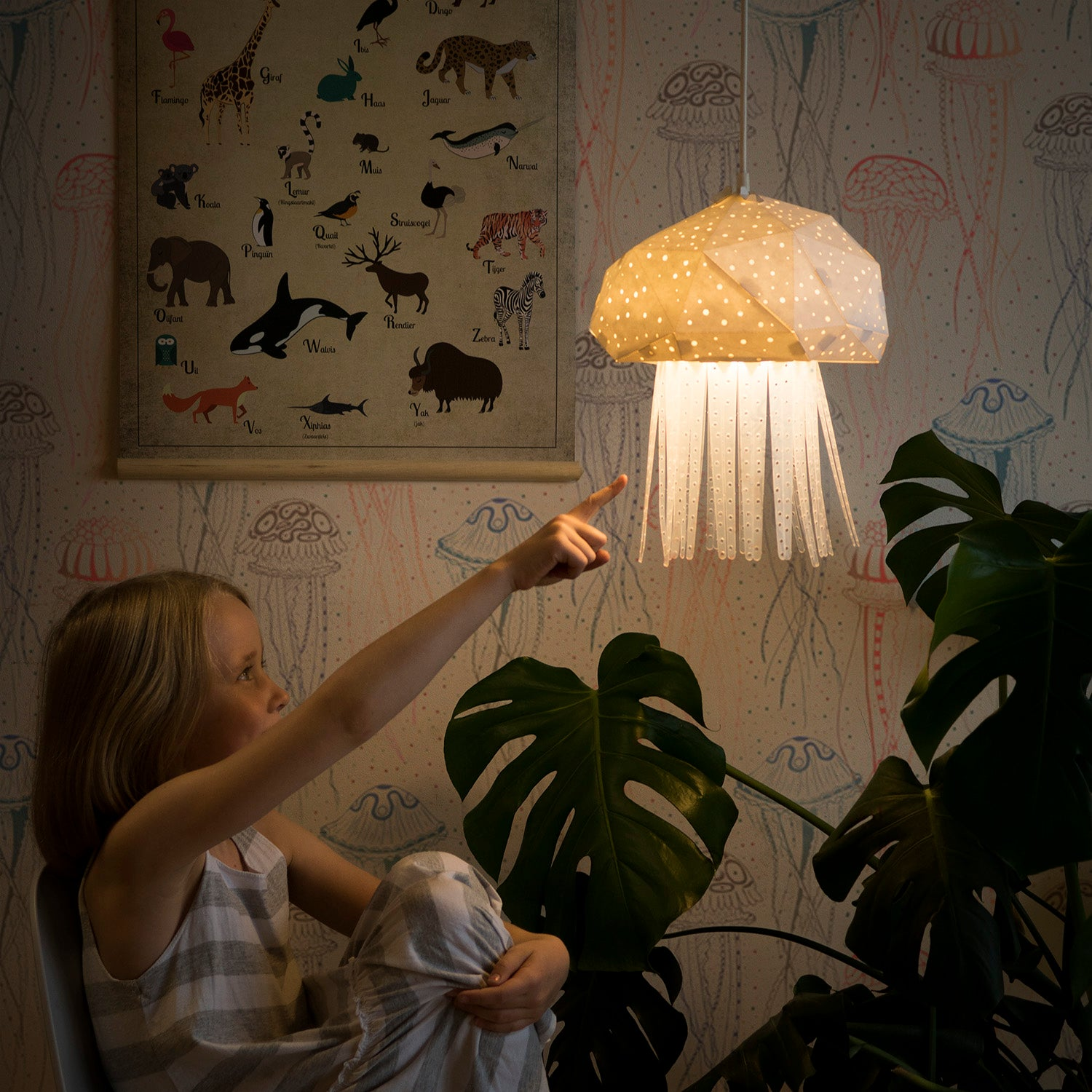 Little girl shows the pendant sea-inspired lamp, which has a shape of little Jellyfish.