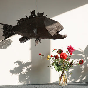 Black lamp in the form of marine fish with sharp teeth hangs above the table, a vase with red flowers is on the table.