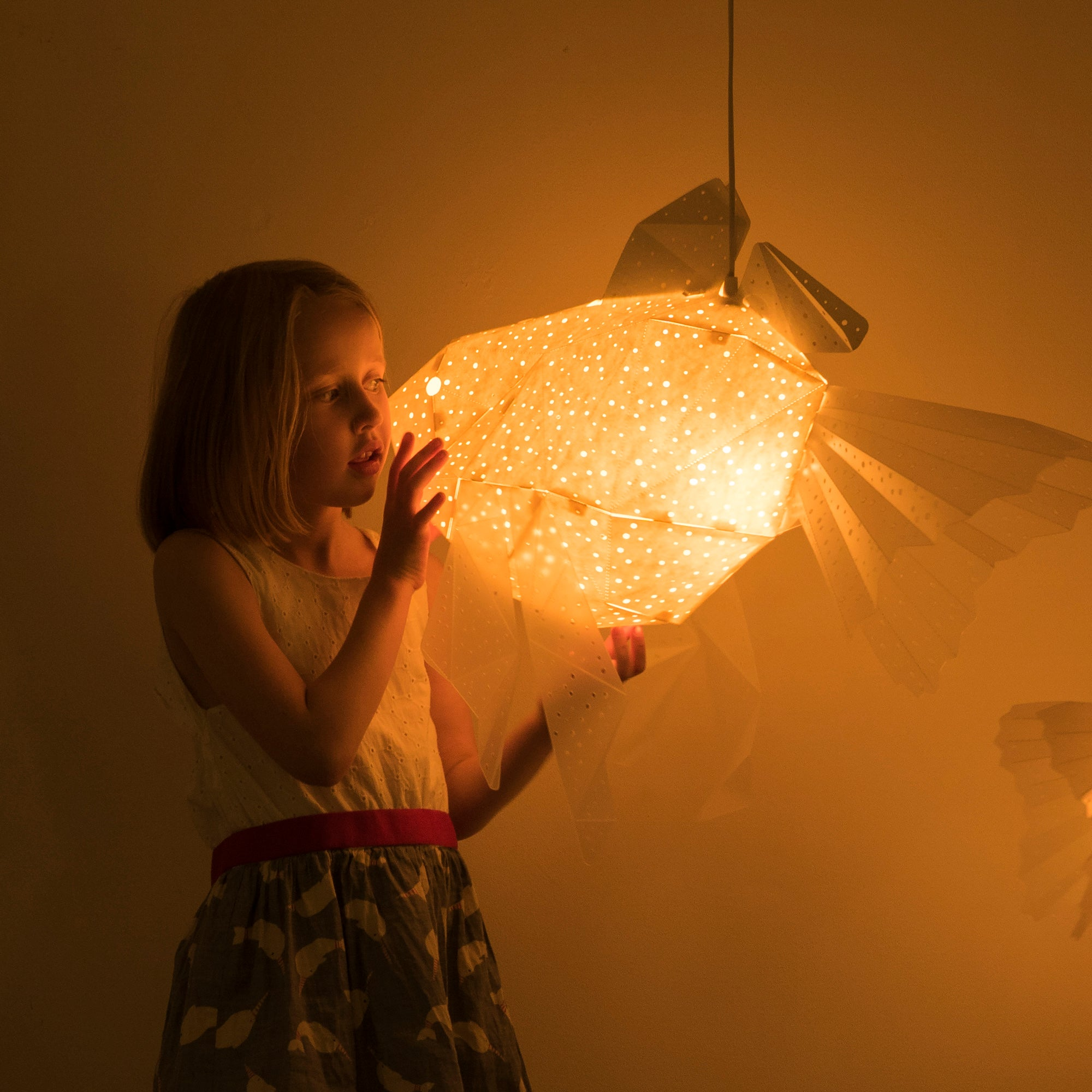 Girl holds the lamp in the form of Goldfish of yellow color, the light is on, dark background.