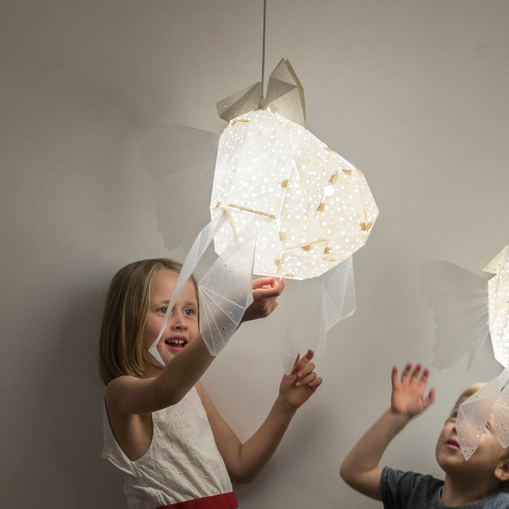 Girl and boy play with the lamp in the form of Goldfish of white color, the light is on, white background.